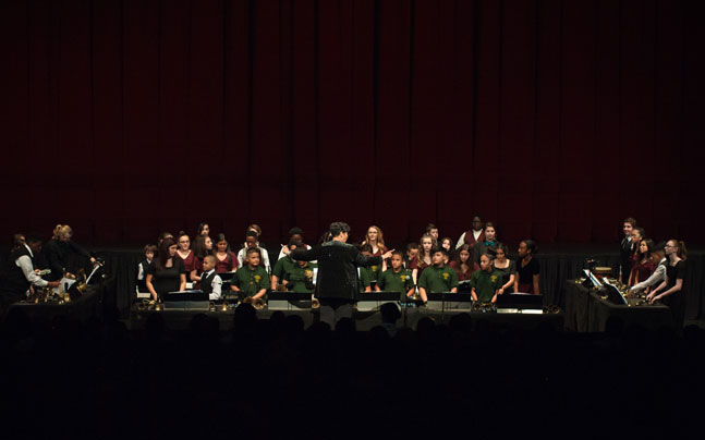 conductor leading kids performing handbells and other bells