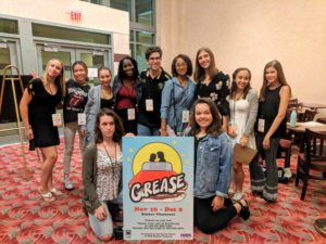 11 Student Critics in Rinker Lobby with Grease sign