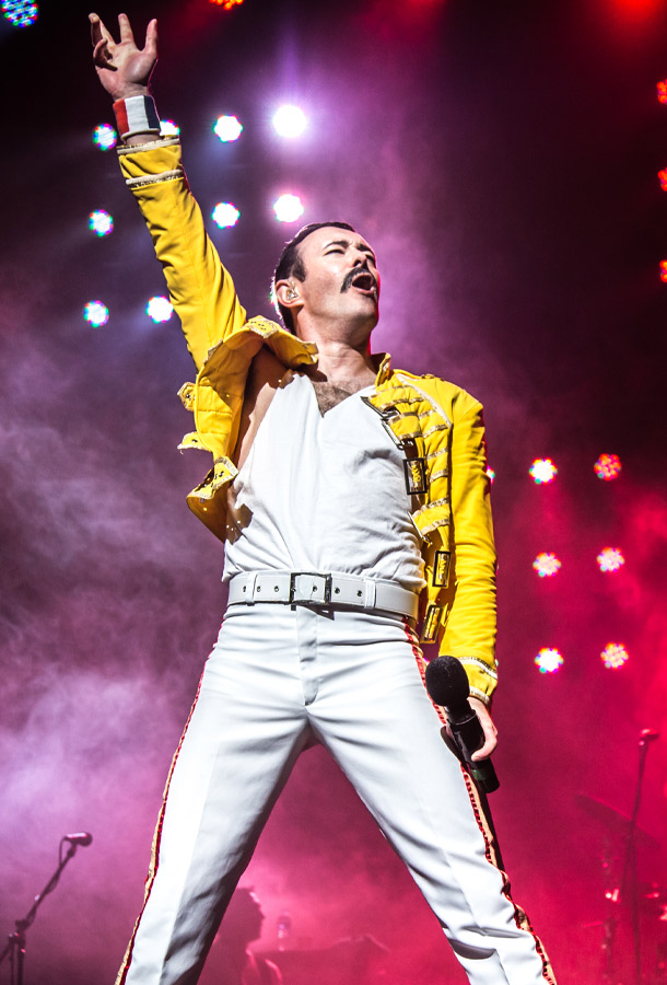 Gary Mullen posing on stage with a microphone, many light surrounding him and fog