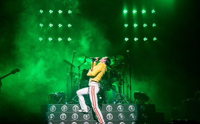 Gary Mullen performing with green lights and fog