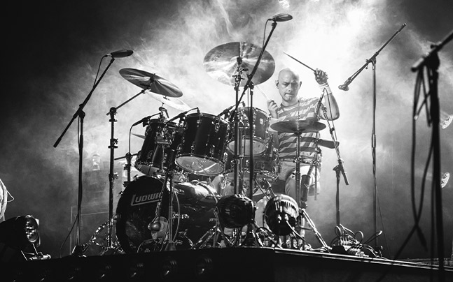 black and white image of drummer drumming, with fog