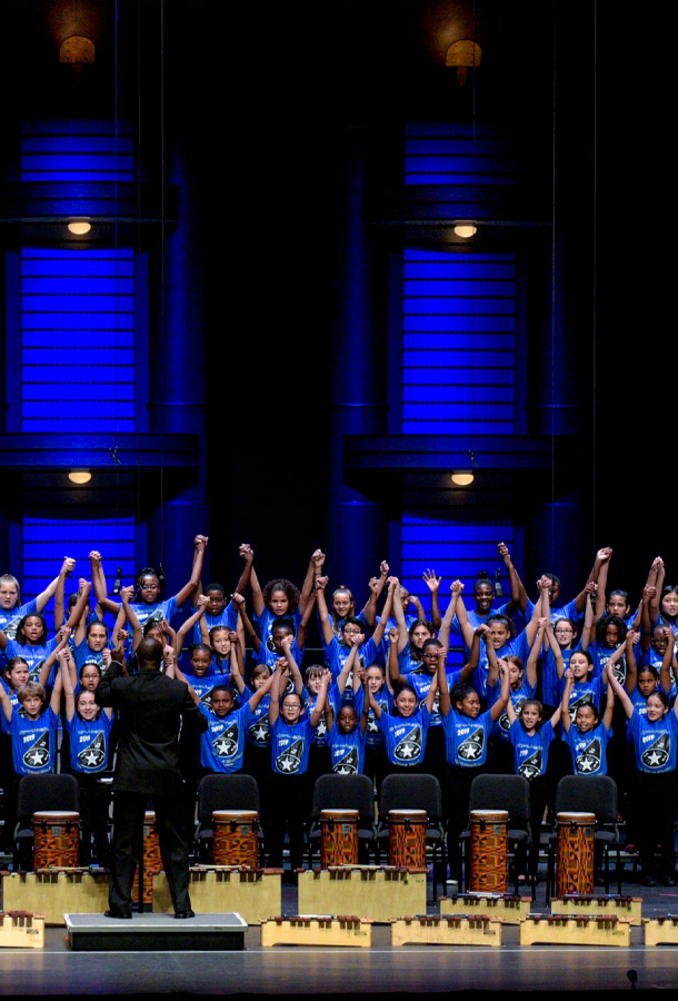 Kids performing on stage with a conductor. Their hands raised up.