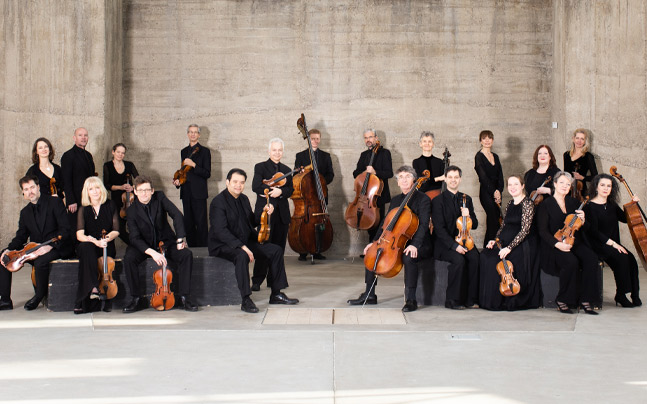 Academy of St Martin posing with their instruments dressed in black