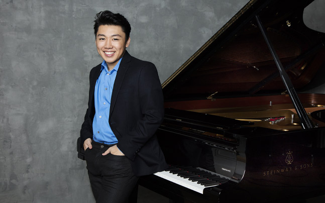 George Li posing by piano. wearing blue shirt and black jacket. Hands in pocket smiling.