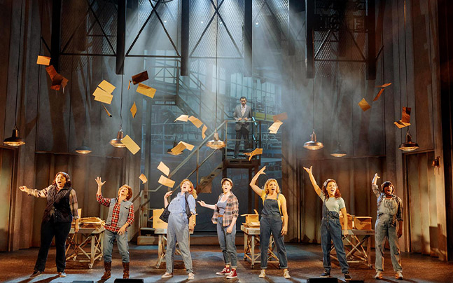 Seven women singing a song, throwing papers in the air.