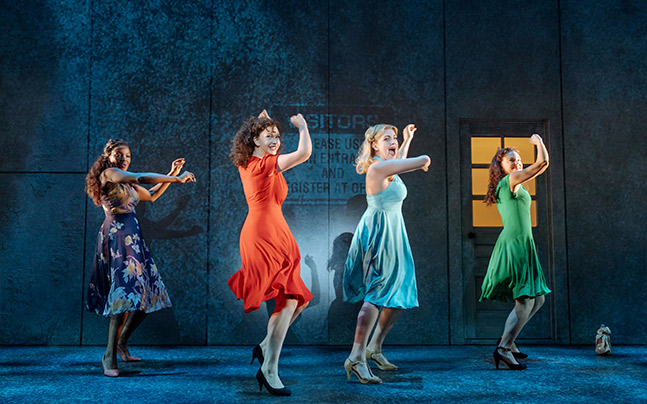 four women dancing in front of a wall.