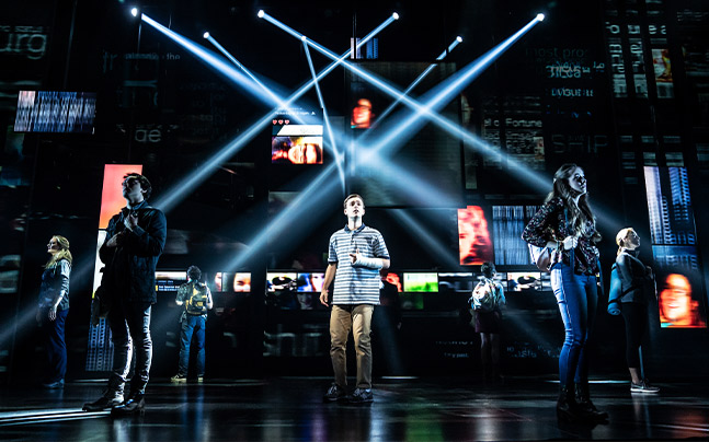 boy standing center stage with blue streams of light shining onto the stage.