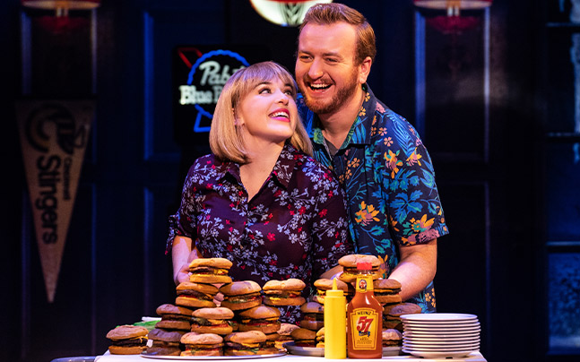 woman gazing up at a man behind a table with a pile of burgers