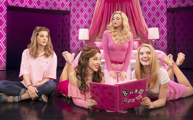 Gretchen and Karen looking at the burn book. Cady watching from the side, Regina staring at Cady. All of them in Regina's bedroom