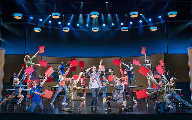 Damian performing a dance number with the ensemble posing with cafeteria trays around him.