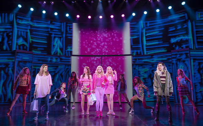 Cady Heron and Janis Sarkisian performing a song with Gretchen Wieners, Regina George, and Karen Smith standing behind them