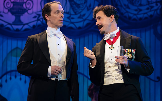 Two men dressed in tuxedos chatting. One has many medals seen on his coat, and around his neck.
