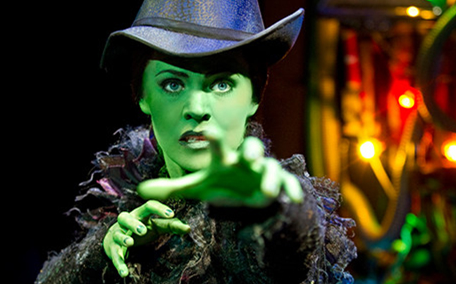 Elphaba arms stretched out, looking concerned