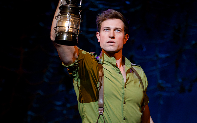 Fiyero looking into the distance with a lantern