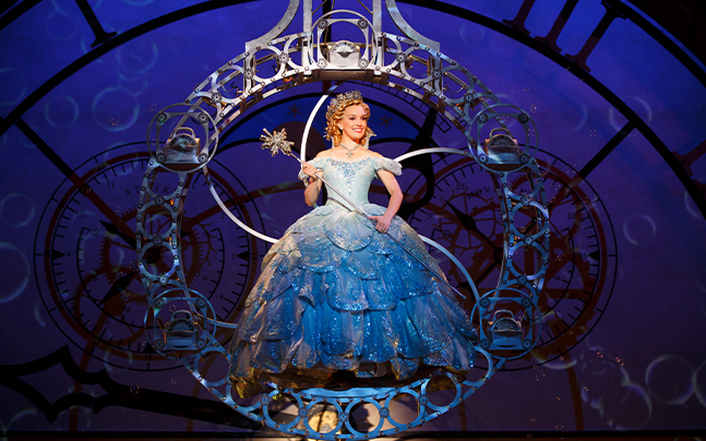 Glinda floating in the air with a blue ballgown, crown, and staff.