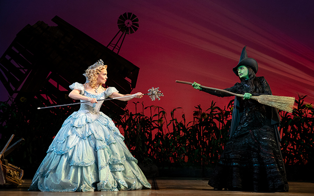 Glinda and Elphaba standing extending out their staff and broom, pointing them at eachother