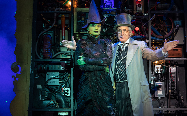 Elphaba and the Wizard looking into the distance in front of an electrical wall