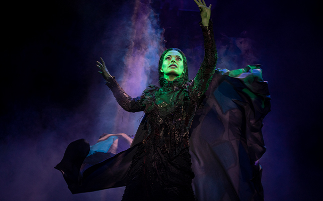 Elphaba looking up with her arms raised. Smoke hazing behind her