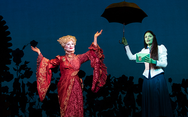 Madame Morrible standing with her arms raised, Elphaba holding an umbrella up.