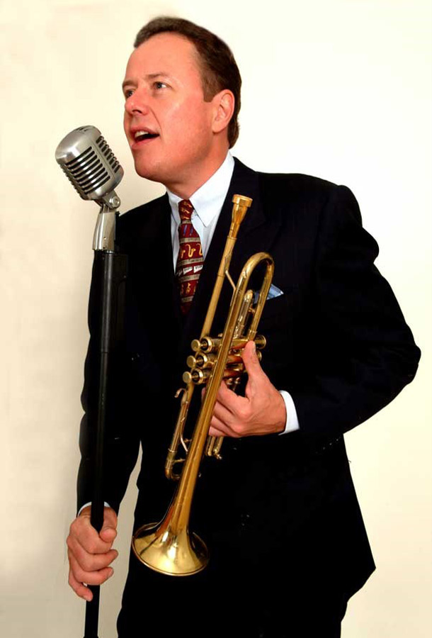 Bob Merrill holding trumpet and microphone stand talking.