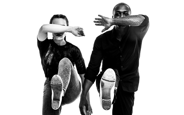 Male and female dancers covering face with arm. Legs up in the air showing bottom of the their tap shoes.