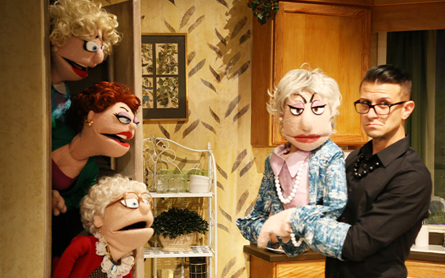 Puppet characters of the Golden Girls peaking in kitchen and looking at other character with handler.