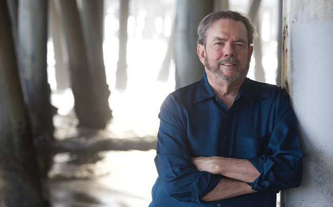 Jimmy Webb leaning on pier column with arms crossed.