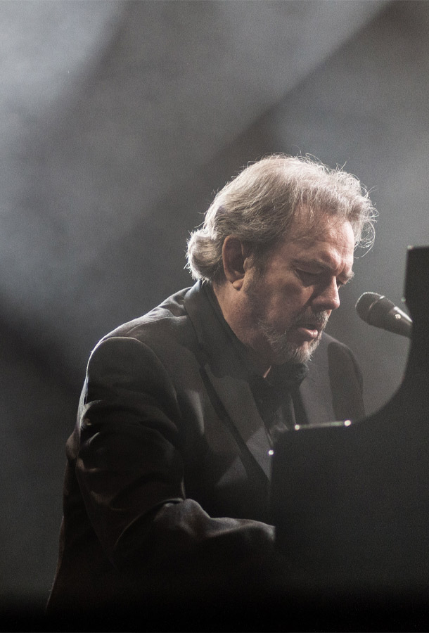 Jimmy Webb in black suit at black piano, haze in the air.