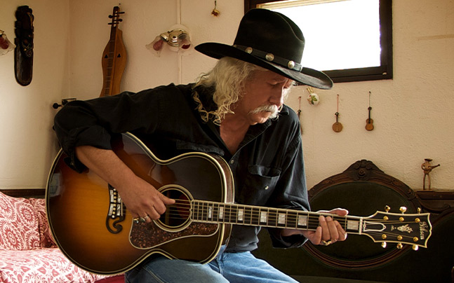 Man wearing cowboy hat playing the guitar while sitting on a stool
