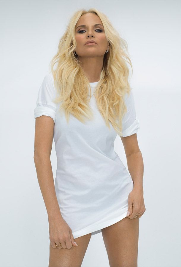 Kristin Chenoweth wearing a long white t-shirt while staring into the camera.