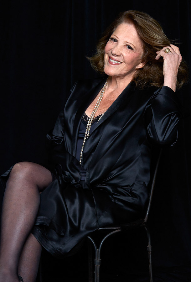 Linda Lavin in black satin robe seating in chair smiling with hand in hair.