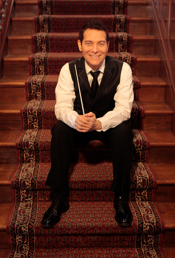 Michael Feinstein siting on carpeted staircase.