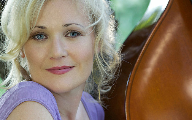 Headshot of Nicki Parrott wearing purple shirt and holding a string instrument.