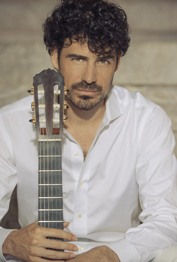 Pablo Villegas headshot with string side of guitar.