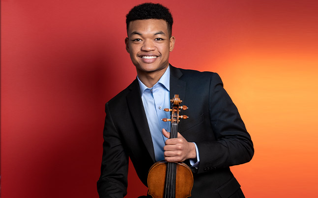 Randall Goosby posing with violin, smiling in front of orange/red backdrop.