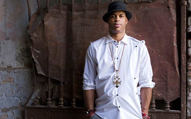 Roberto Fonseca posing for camera wearing white shirt, necklace and hands in pocket.