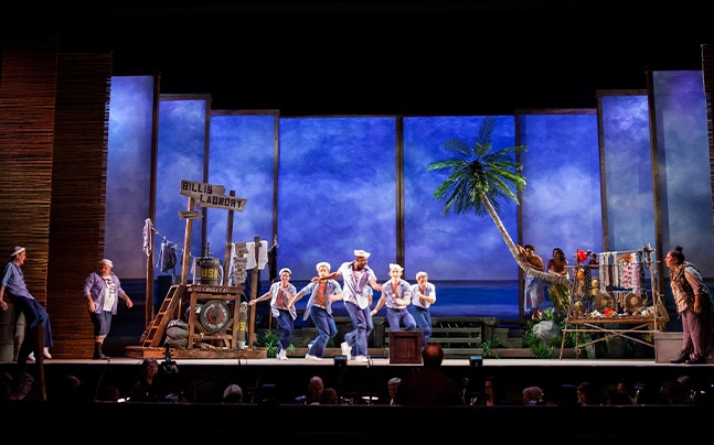 Five Sailors dancing on stage in front of a tropical set
