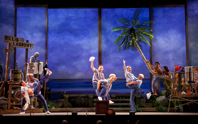 6 sailers onstage dancing in front of a tropical set