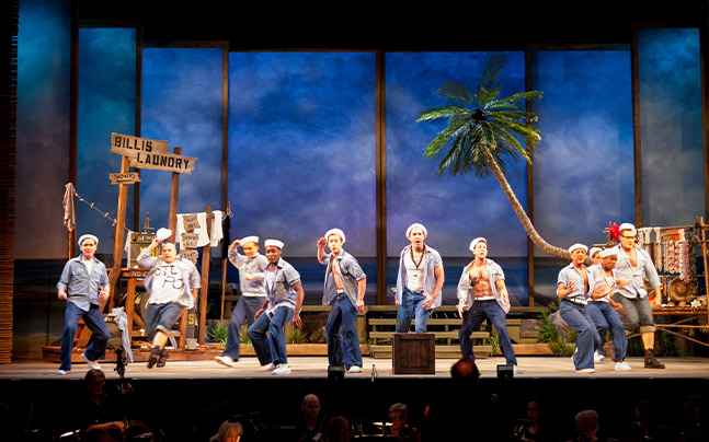 Eleven sailors dancing on stage in front of a tropical set