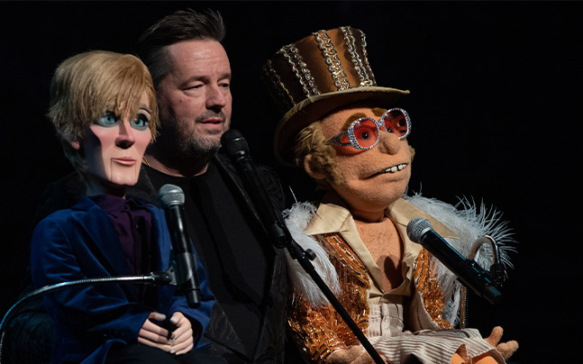 Terry Fator holding two of his puppets on stage. All three have microphones