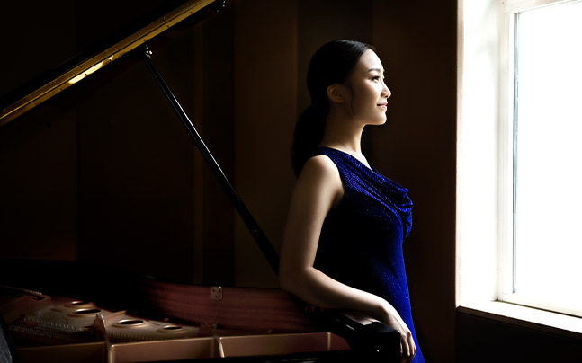 Yi-Nuo Wang in blue dress looking out window while leaning on open piano.