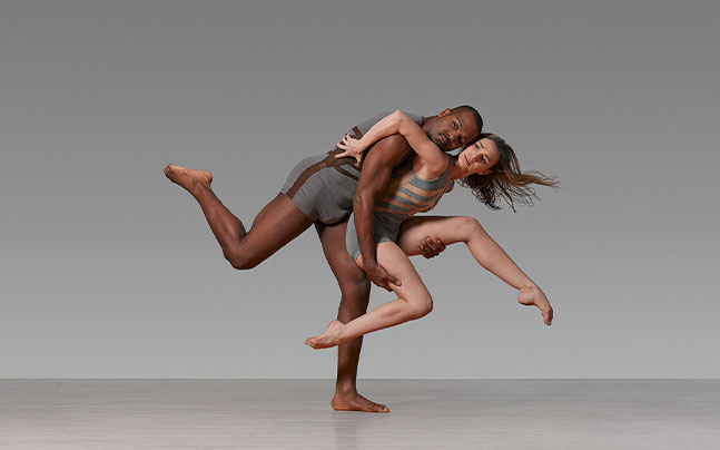 a man and a woman in gray suit doing ballet together