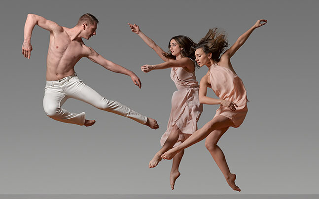 a man in white pants and 2 woman in light pink dress doing ballet together