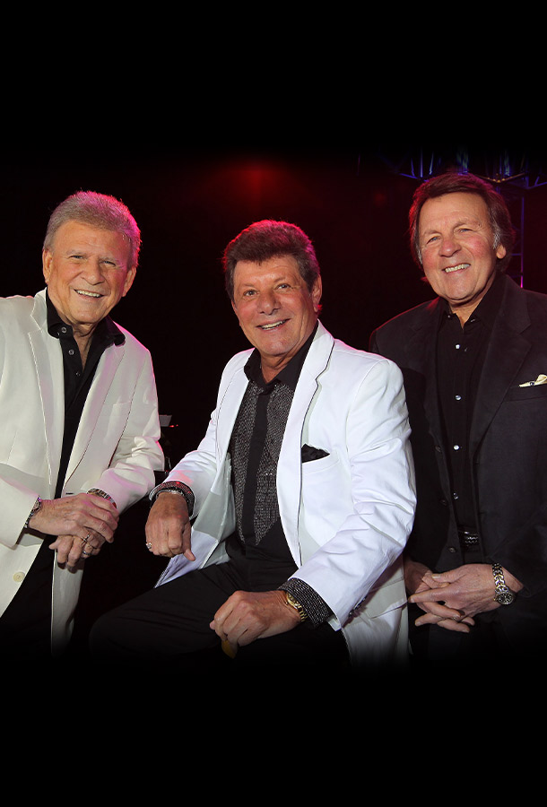 Three men smiling at the camera in front of a stage. All wearing formal jackets and pocket squares