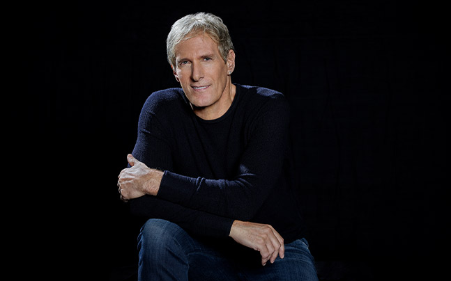Michael Bolton posing in a black sweater and Jeans in front of a black background