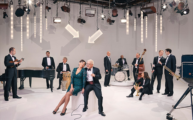 band of musicians chatting together on a white set. Two lead singers sit together in the center on a cube. Overhead lights and arrows are point down all above them.