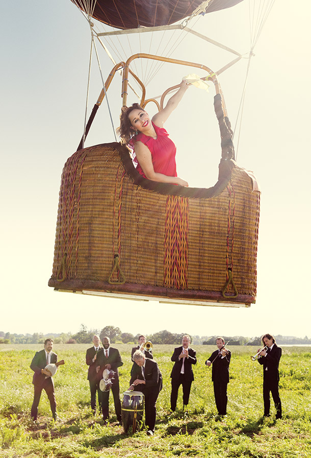 Woman smiling inside of a hot airballoon that is floating up. Musicians dressed in suits playing below them in a grassy field.