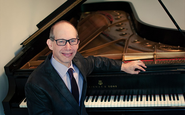 Ted Rosenthal in suit siting by open piano smiling.