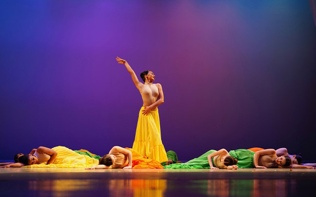 Female dancer in yellow dress in pose while other female dancers in yellow and green dresses lay on floor next to her.