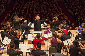 conductor and orchestra performing with an audience